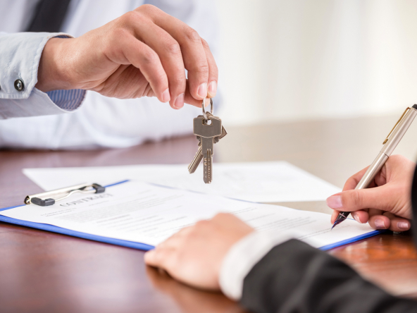 Real estate agent handing keys to new owner, who is signing paperwork