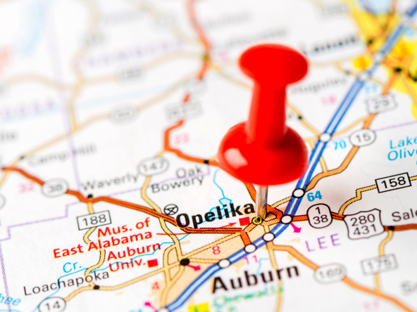 Paper map with pinpoint on Opelika and Auburn, Alabama